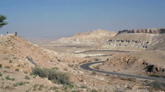 Panoramic view Makhtesh Ramon crater, desert, ibex, people walk on road Stock Footage