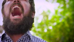 Dolly shot portrait of a bearded man screaming out loud in anger Stock Footage