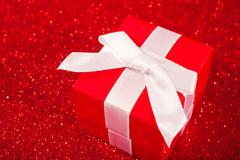 Red gift boxes on glitter red background - stock photo