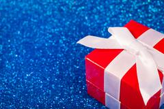 Red box with christmas gift on shiny glitter blue background - stock photo