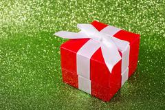 Christmas gift against a magical glitter shiny background with copy space - stock photo