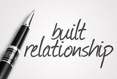 pen writes built relationship on white blank paper - stock photo