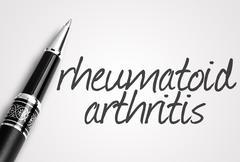 Pen writes rheumatoid arthritis on white blank paper Stock Photos