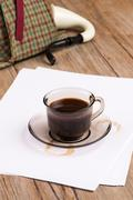 Coffee cup, paper sheets and detective hat - stock photo