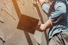 plasterer concrete worker at wall of home construction building - stock photo