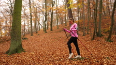 Woman doing nordic walking in forest steadicam 4K. Stock Footage