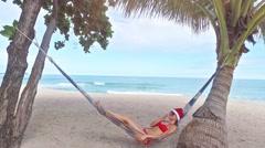Beautiful Caucasian woman in Santa hat and red bikini  relaxing on beach  Stock Footage