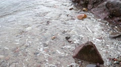 Small waves hit rock on the Northsea Beach Stock Footage
