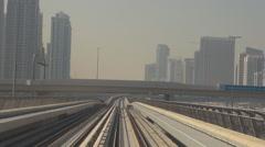 POV Point of view metro train pass Dubai city tall skyscraper people commute day Stock Footage