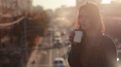 Beautiful woman drinking coffee on a city bridge Stock Footage