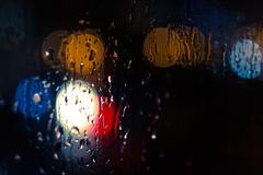 Car headlamps and street lights at night create bokeh style defocused blurs a - stock photo