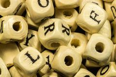 Macro close-up of many hand painted handicraft alphabet wooden beads with ass Stock Photos