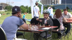 Father and son play chess in outdoor family tournament. 4K Stock Footage