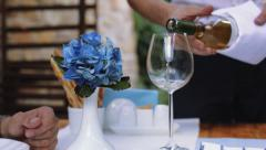 Romantic dinner date pouring white wine and clinking glasses - stock footage