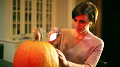Woman preparing to carve pumpkin Stock Footage