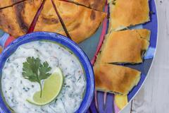 Greek tzatziki and pastry on a colorful plate - stock photo