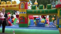 Children have fun on inflatable blow up toy playground. 4K Stock Footage
