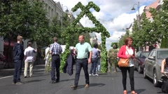 Stock Video Footage of Oak leaves decorated entrance to herbal fair and people walk. 4K