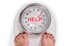 Low section of woman on weight scale with help text over white background Stock Photos