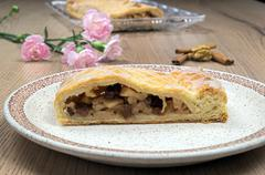 Homemade strudel with walnuts and carnations on a plate, food, cinnamon - stock photo
