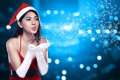 Asian woman in santa claus costume blowing magic dust Stock Photos