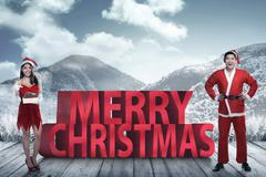 Asian couple in santa claus costume posing on merry christmas text - stock photo