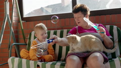Stock Video Footage of Boy and Grandmother Popping Soap Bubbles