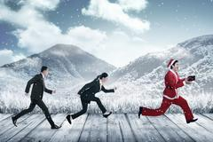 Business people chasing santa claus Stock Photos