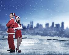 Happy couple in santa claus costume standing on the building rooftop Stock Photos