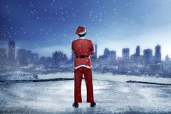 Asian man wearing santa claus costume standing on the building rooftop Stock Photos