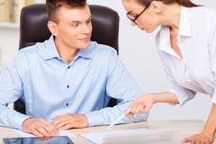 Officeman admires his assistants beauty instead of working - stock photo