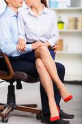 Office assistant is sitting on coworkers lap Stock Photos