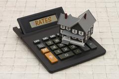 Home Mortgage Interest Rates, A gray house and calculator on stone background Stock Photos