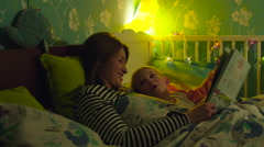 Mother Reading a Book to Son before Sleep Stock Footage