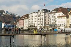 Stock Photo of People walk by the bridge in Lucerne, Switzerland.