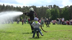 Fire fighter spray water from hose and kids run under water drop. 4K Stock Footage