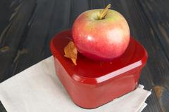 Red apple and a closed box for school lunch Stock Photos
