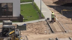 Worker pressure sand for tiles sidewalk with plate compactor. 4K Stock Footage