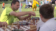 Father teach son play chess in outdoor family tournament. 4K Stock Footage