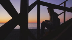 Travel: Silhouette of beautiful girl tourist drawing sunset at the beach. Medium Stock Footage