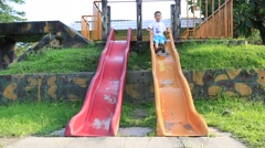 Young Asian boy on slippery slide in playground - stock footage