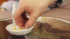 Hand is taking pharmaceutical pill from plate Stock Footage