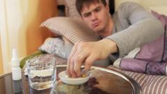 Sick man taking pill while lying on bed Stock Footage