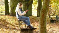 Woman is reading a book on a bench in autumn Stock Footage