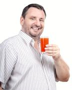 Middle aged man is fond of detox smoothie - stock photo