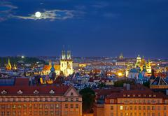 Prague cityscape at night time with full moon - stock photo