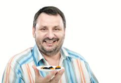 Stock Photo of Smiling man likes dried fruits