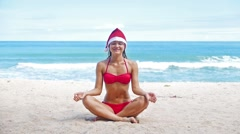 Young christmas woman in santa hat and red bikini doing yoga Stock Footage