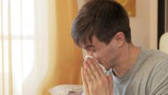 Ill man blowing his nose in yellow room Stock Footage