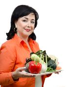 Smiling nutritionist with a tray of fresh vegetables - stock photo